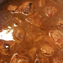 Væsken fra panden, lidt mere øl og oksefond røg på kød og urter til det dækkede. Jeg brugte et par stykker af de der Fond du Chef fra Knorr. Det var hvad køkkenet kunne byde på, men man kan jo fint koge sin egen fond, hvis man har tid.